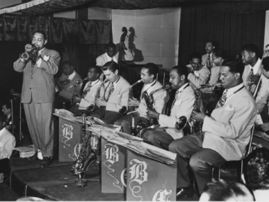 Benny Carter leads his orchestra on trumpet
