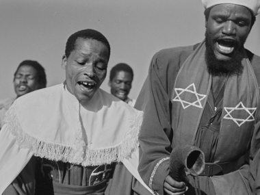Men Singing, 1946. Two men are standing beside each other singing. Both are wearing robes; the one on the right has the Star of David on his robe and is holding a ram's horn which is a wind instrument.
