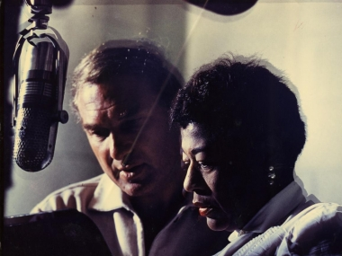 Ella Fitzgerald and Norman Granz at microphone, color photoprint, Archives Center, National Museum of American History, Copyright probably retained by creator.