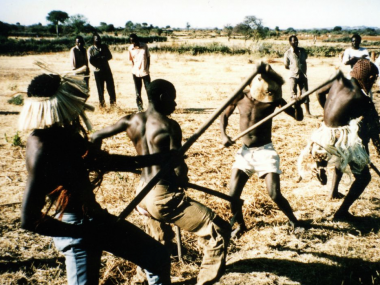 The farmers from the Bagobogobo farming group in Miswaki village, Shinyanga district, practice a dance routine at the farm site, which they will use in the forthcoming post-harvest dance competitions. 1994, photo by Frank Gunderson