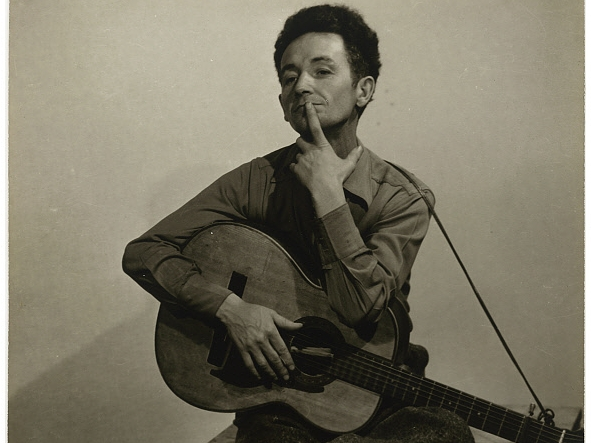 Woody Guthrie with guitar.
